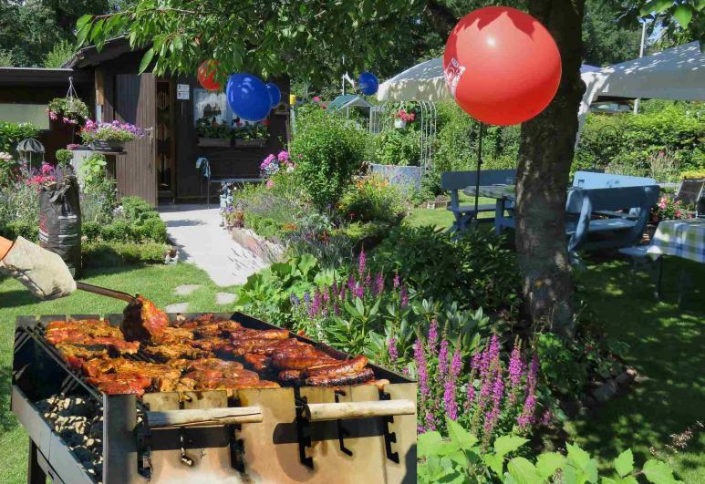 Blick auf einen Garten, wo ein Griller mit Fleisch steht
